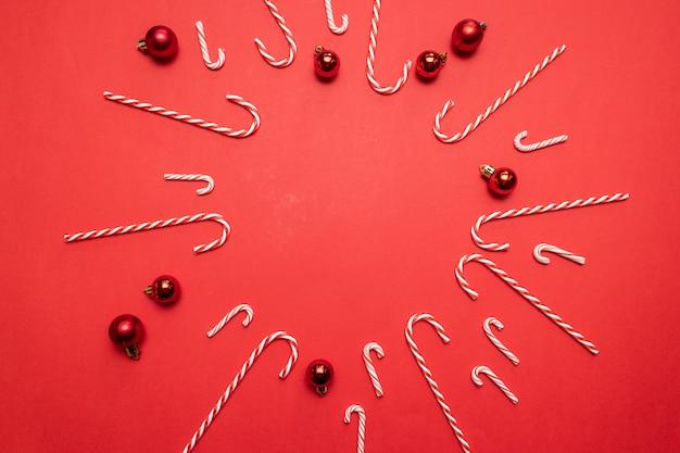 赤いボールと赤のキャンディーのフレームとメリークリスマスとハッピーホリデーバナー。グリーティングカードテキストデザイン