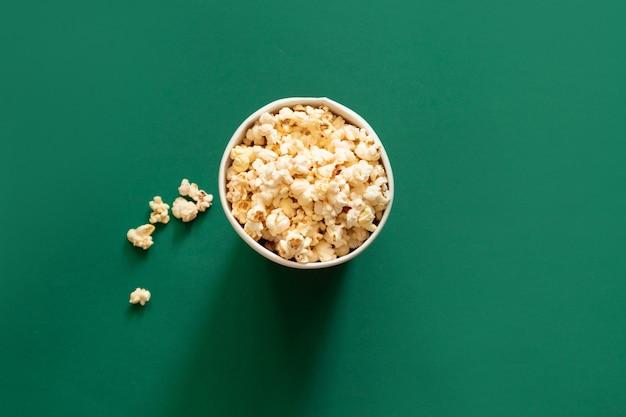 Попкорн в бумажный мешок на зеленом фоне. концепция нездоровой диеты.
