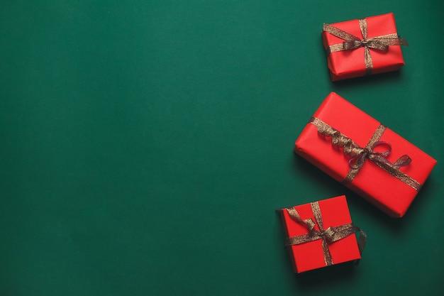 クリスマスバナー。緑の背景にゴールドリボンとクラフトの赤いギフトボックスクリスマス背景デザイン
