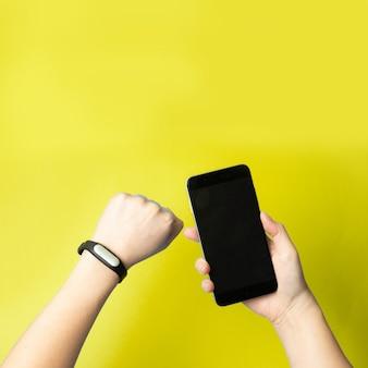 女性の手は、スマートフォンとフィットネスブレスレットを手に持っています。