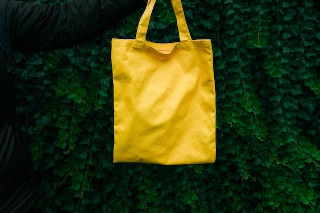 緑の植物の背景に手作りの買い物袋。空白のキャンバスバッグ、手でデザインのモックアップ。