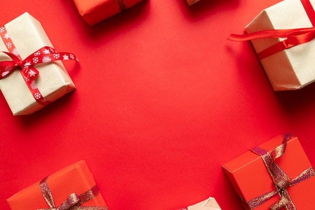 赤い背景の上面にクリスマスクラフトの手作りギフトボックス。冬の休日のテーマ。フラット横たわっていた。