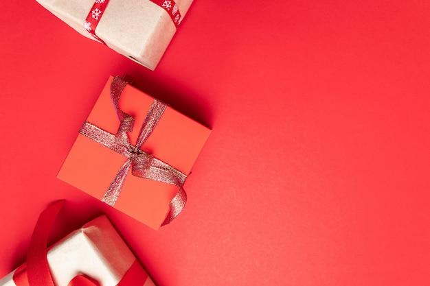 モダンなギフトまたは赤の背景の上面に金の弓と星の紙吹雪が付いているボックスを提示します。誕生日、クリスマスや結婚式のフラットレイアウト構成。