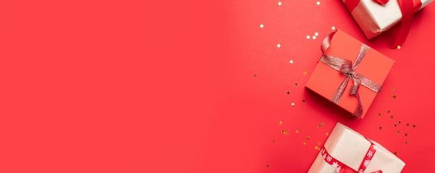 ギフトまたは創造的な構成は、金弓と赤い背景の上面に星の紙吹雪とボックスを提示します。誕生日、クリスマスや結婚式のフラットレイアウト構成。