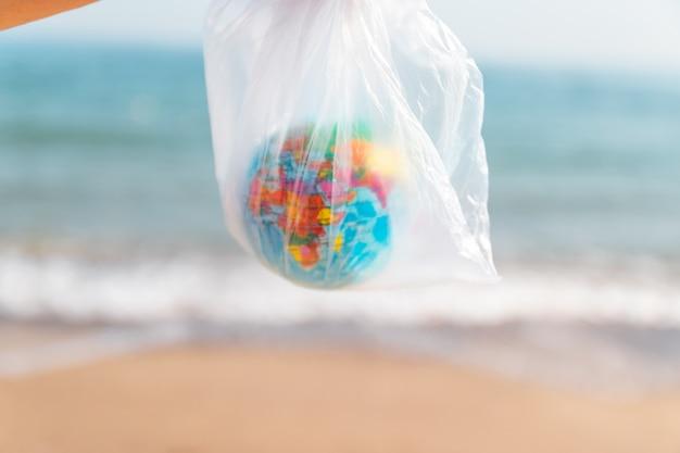 環境汚染の概念。女性は彼女の手でビニール袋と海の背景に地球を保持しています。