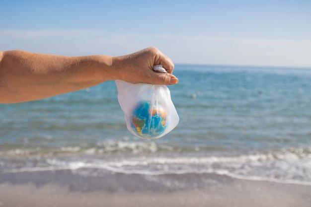 女性は海の背景にビニール袋と地球を手します。