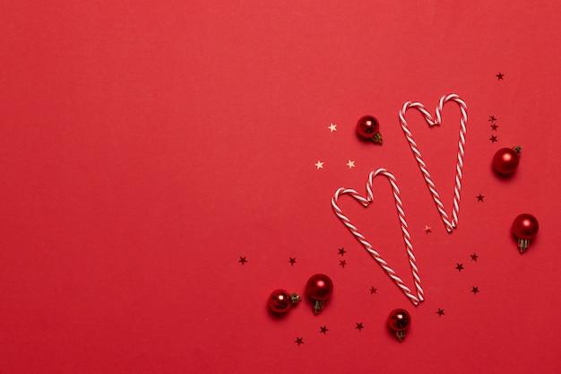 クリスマスの組成物。赤の背景に愛の形でキャンディー。クリスマス、冬、新年のコンセプト。フラット横たわっていた、トップビュー、コピースペース