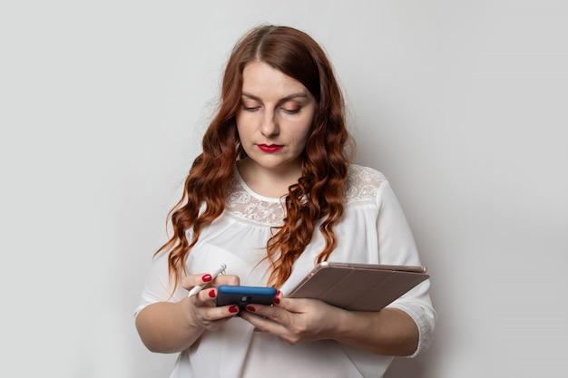 美しい巻き毛のヘアスタイルを持つ若いビジネス女性は、スマートフォンを使用して、タブレットを保持しています。プロジェクトと仕事。自信を持ってビジネスの専門家。