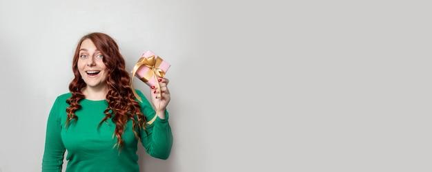 Радостная милая кудрявая девушка в зеленом свитере и подарочная коробка в руках на фоне серой стены
