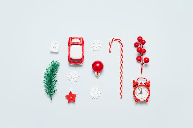Плоская планировка декора рамки с елкой ветка, часы, веточка с ягодами, игрушечная машинка, конфета на синем фоне