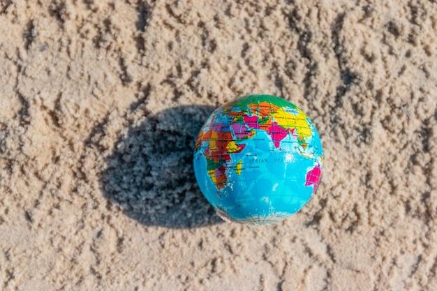 砂の背景に作られた地球。世界アースデイのコンセプトである世界、創造、環境汚染を救います。
