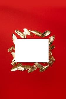 Творческая вертикальная композиция с белым пустой шаблон открытки с золотыми листьями на красном фоне.