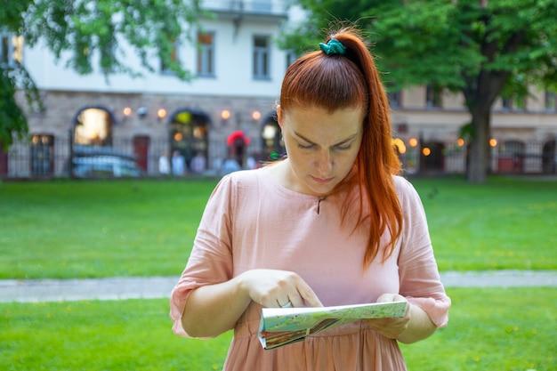 ピンクのドレスを着た赤髪の女性が地図を持ち、公園を探索する