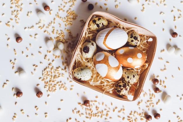 Ассорти золотых пасхальных яиц, шоколадных драже и проса в корзине на белом