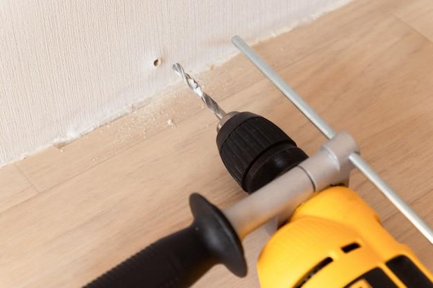 Электрическая желтая дрель с алмазным сверлом и отверстием в стене в доме. ремонт дома концепции.