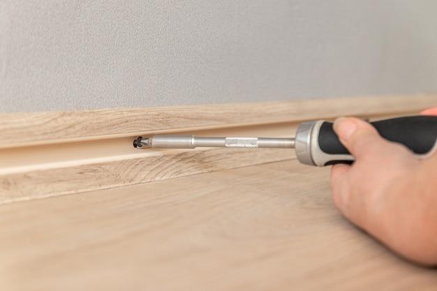 Женская рука затягивает винт с помощью отвертки в стене. ремонт в доме