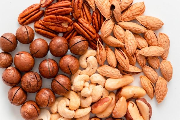 灰色の背景に茶色のナッツの盛り合わせ。マカダミ、カシューナッツ、みじん切りアーモンド、ピーカンナッツの健康食品