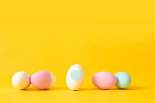 Хв. украшенные белые, розовые и синие яйца на желтом фоне.