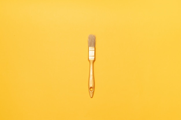 黄色の背景上に描画するための金のブラシ