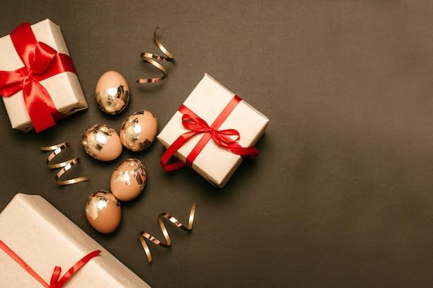 Золотые яйца с сюрпризом подарочные коробки на темном фоне с местом для текста. красная лента банты украшения. праздничная пасхальная композиция