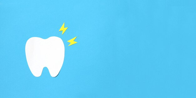 紙の歯の置物と青色の背景に黄色の稲妻。歯痛のコンセプト