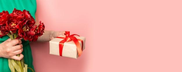 女性の手は赤いチューリップの花束のギフトボックスを保持します。バレンタインデーのコンセプト