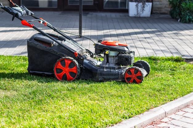 裏庭で緑の草を刈る芝刈り機。庭の清掃サービス。