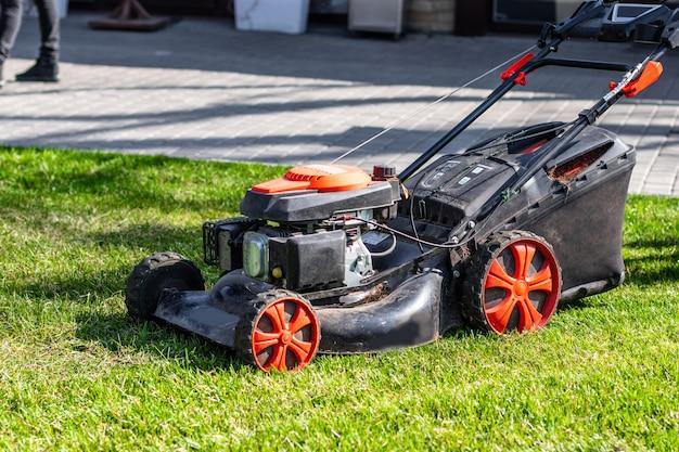 晴れた日に裏庭の緑の草を刈る芝刈り機。