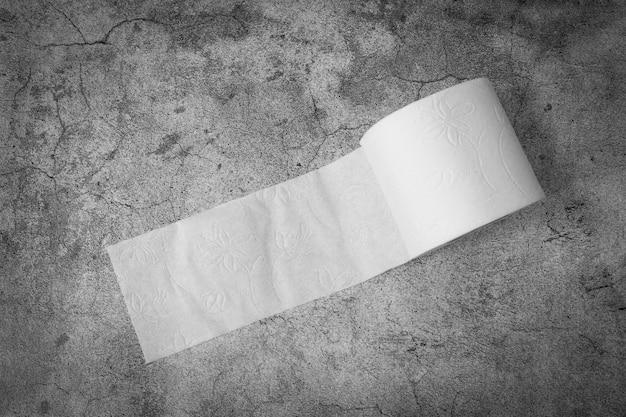 テーブルの上のトイレットペーパーのロール。下痢、便秘または消化器系の問題の概念。