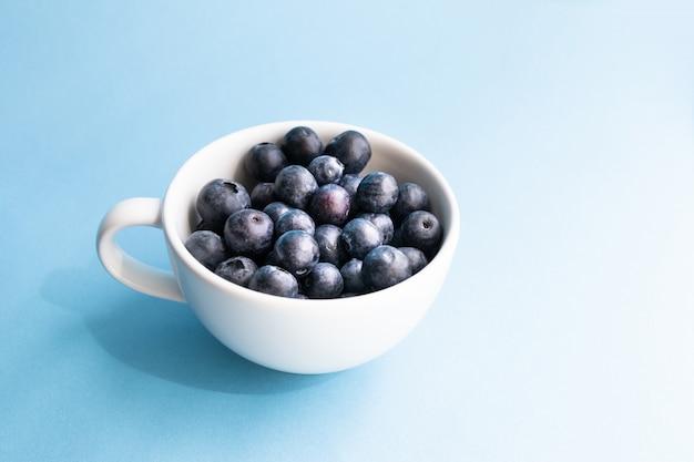 青い表面にマグカップで新鮮な生の有機ブルーベリー