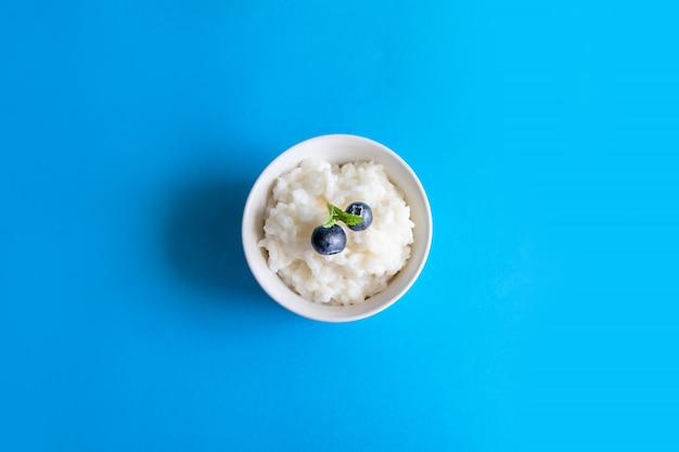 Вкусная рисовая каша с ягодами черники в белой миске на синем фоне. правильная концепция здорового завтрака