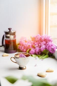 白い磁器のライラックブーケと美しい磁器のカップで新鮮な熱い紅茶