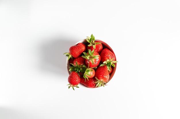 白い背景の上に新鮮なイチゴをボウルします。夏の構図