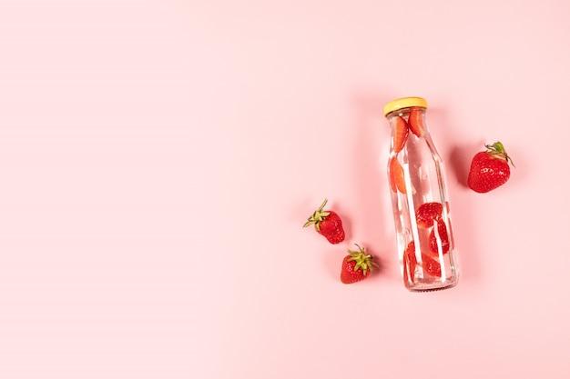 ピンクの背景の新鮮なイチゴの夏のフルーツとデトックス水、カクテル、レモネードまたはお茶のボトル。夏の構図、最小限のスタイル