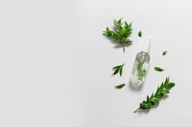 Природные косметические пластиковые бутылки с жидкостью и зелеными листьями на сером фоне. натуральные косметические средства