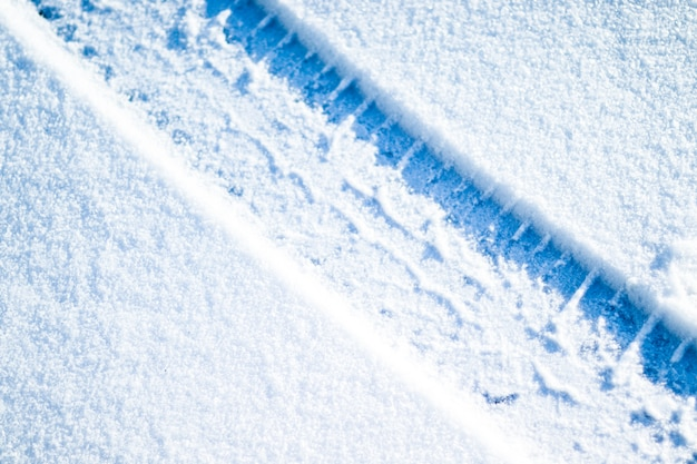冬の道路上の車のタイヤ。雪のクリスマス冬の背景