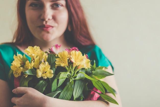 Красивая молодая женщина в зеленом платье держит букет весенних цветов