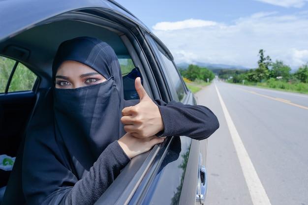 道路で車を運転しているサウジアラビアの女性。