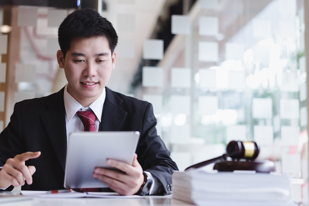 オフィスの木製机の上の真鍮スケールを持つ連絡先の顧客に携帯電話を使用してビジネス弁護士。法律、法律サービス、アドバイス、相談、正義。