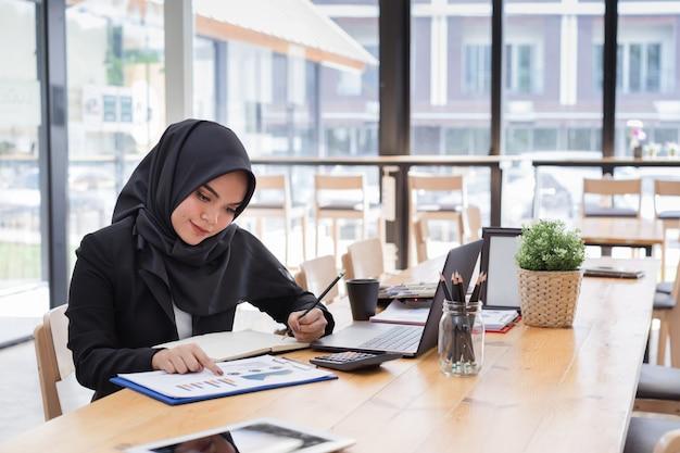 コワーキングで働く黒ヒジャーブを着ている若いイスラム教徒のビジネス人々の肖像画。