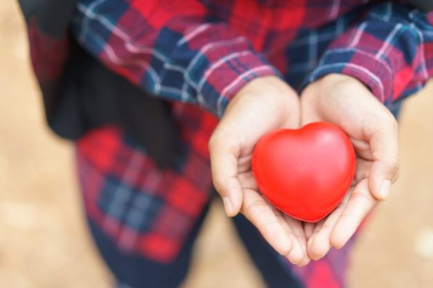 赤いハート、健康、薬、慈善を与える女性の手。