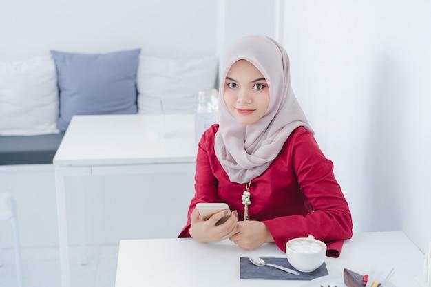 Портрет счастливой молодой мусульманской женщины используя ее мобильный телефон.