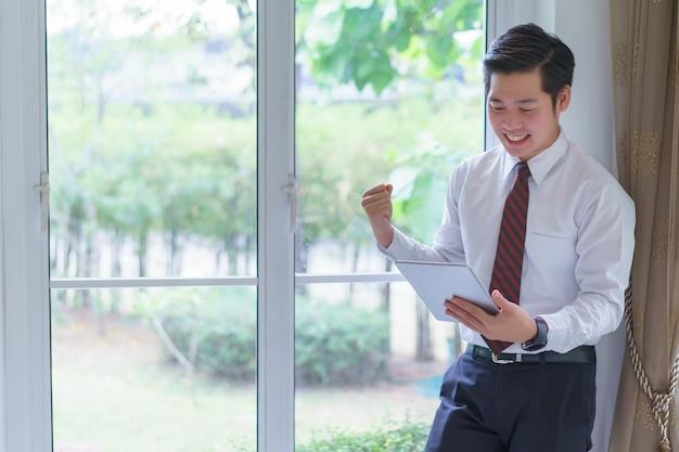 高収益を喜んで受け取るタブレットを使用して幸せなアジアの若いハンサムな実業家は、独自の繁栄しているビジネスをしています。