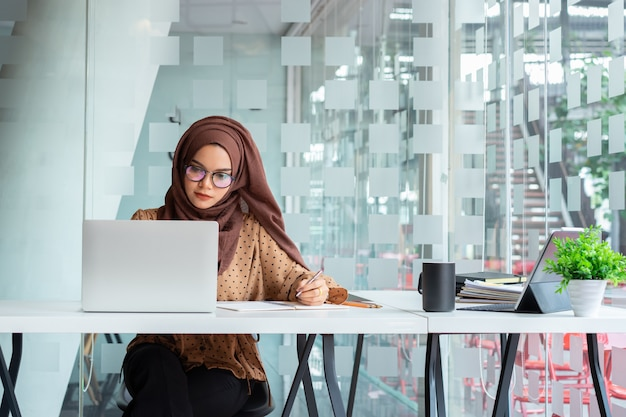 ビジネスを議論し、創造的なコワーキングに座って笑顔のスマートカジュアルな服装の若いアジアのイスラム教徒のビジネス女性。