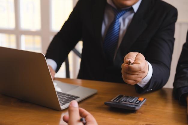 会議室でカメラにペンを指してビジネスマン。