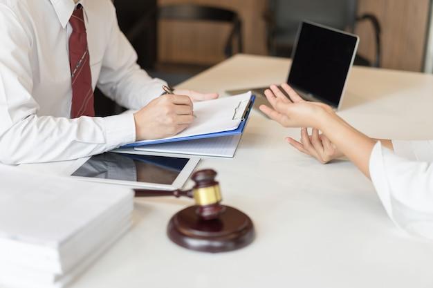 法律と規制についての男性弁護士とビジネスマンの顧客との間の協議。
