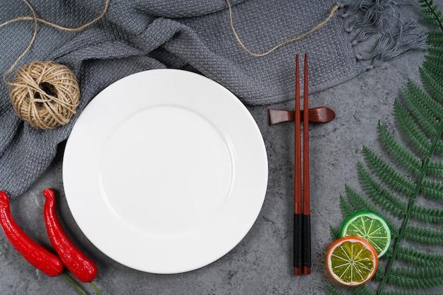 白い皿、赤唐辛子、レモンスライス、箸を空にします。グラフィックモンタージュの白いプレートを空にします。トップビュー、フラットレイアウト。
