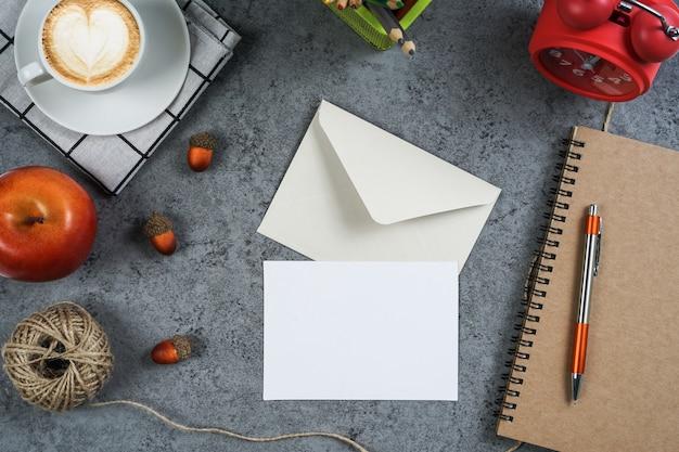 空の白いグリーティングカードとコンクリート表面の封筒。トップビュー、フラットレイアウト。