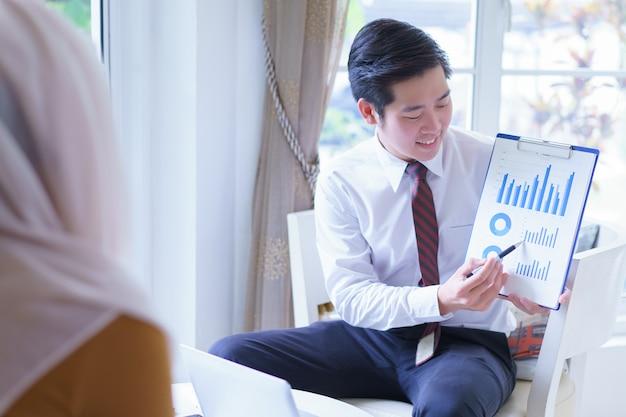 会議やオフィスでの交渉でグラフレポートを提示する幸せなビジネスマン。