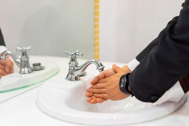 Бизнесмен моет руки в ванной комнате